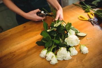 Female florist trimming flower stem at her flower shop