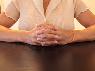 Female with manicured nails clasping hands at a desk in an office during a job interview.
