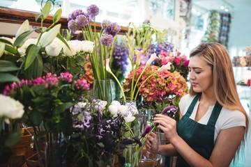 Female florist arranging flowers at her flower shop
