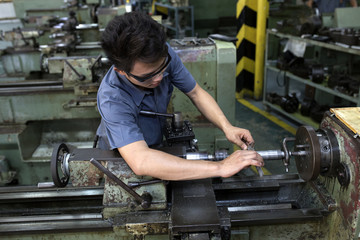 technician worker at metal machining  milling lathe in tool work