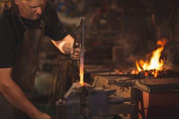 Blacksmith working on a heated iron rod