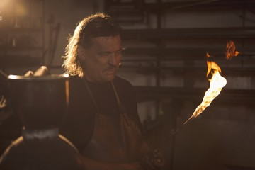 Blacksmith holding a welding pipe