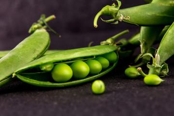 fresh green sweet peas  on black stone background