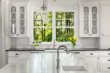 White Kitchen Detail in New Luxury Home: Kitchen Island Quartz with Sink and Cabinetry in the Background, with a View of Radiant Green Trees