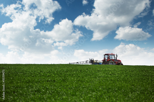 Wall mural Tractor spraying wheat field with sprayer
