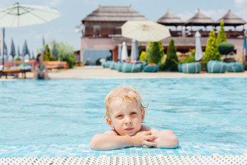 Child leaning on pool's edge