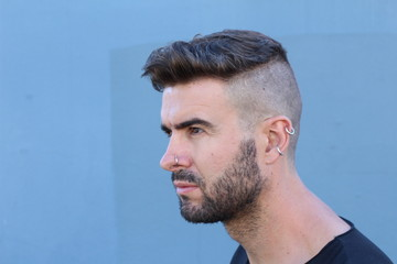 Close up portrait of the profile of a male fashion model with beard and piercing posing on blue background with copy space