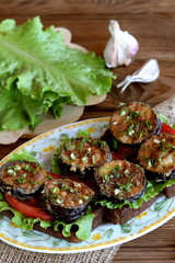 Dark bread toasts with fried eggplant, fresh tomatoes, lettuce, garlic, dill. Green lettuce on the blackboard, garlic. Healthy sandwiches with vegetables on plate on wooden background