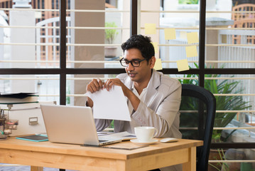 stress looking indian business male at office