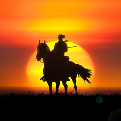 Silhouette of cowboy against the setting sun.