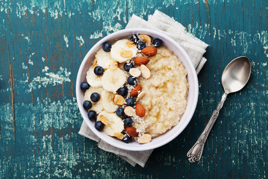 Bowl of oatmeal porridge with banana, blueberries, almonds, coconut and caramel sauce on teal rustic table, hot and healthy food for Breakfast, top view, flat lay