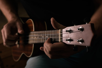 Man plays ukulele. Only instrument and hands are seen
