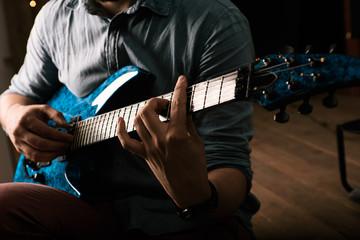 Man in shirt playing electric guitar