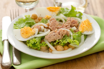 salad chickpeas with fish and boiled egg on white dish