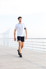 Attractive young sportsman walking on pier