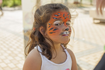 Little girl with her face painted like a tiger
