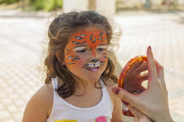 Little girl with face painted looking in the mirror