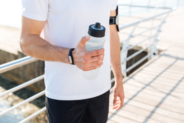 Cropped image of a male sportsman holding water bottle outdoors