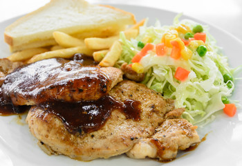 Grilled pork steak fillet with salad and French fries on white plate