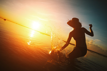 Wall Mural - Woman in straw hat playing with water in the ocean at sunset