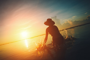 Wall Mural - Silhouette of young woman splashing in water at sunset