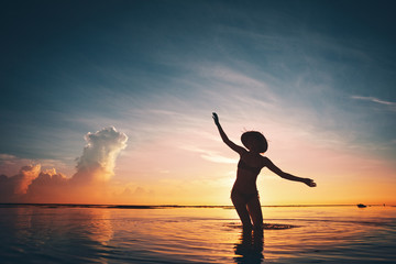 Fotomurais - Silhouette of cheerful woman dancing in the ocean at sunset