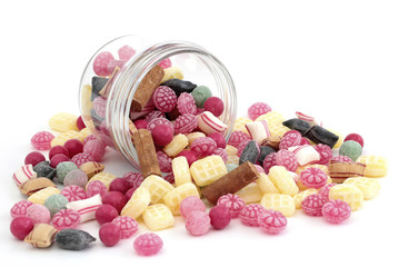 Many colored candy falling out of a jar