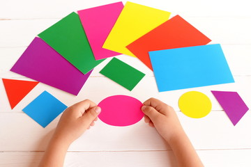 Child holds cardboard pink oval in the hands. Child learns colors and geometric shapes. Developing skills in kids. Reach concept. Different cardboard cards on a table