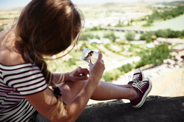 Woman hipster looking at picture in her smart phone sitting on mountain peak. Concept of travel and technology.