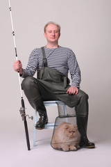 Fisherman in waders sitting on chair, holding a fishing equipment with cat