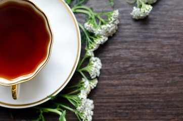 herbal yarrow tea in a porcelain cup on a dark wooden background