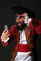 Portrait of surprised man in a pirate costume with mobile phone