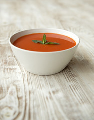 Tomato soup in a bowl with basil leaves on top on a wooden surface