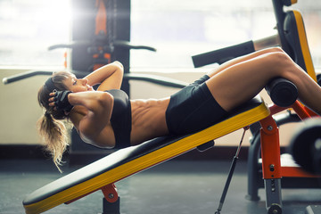 athletic fitness woman doing some crunches in a bench at the gym