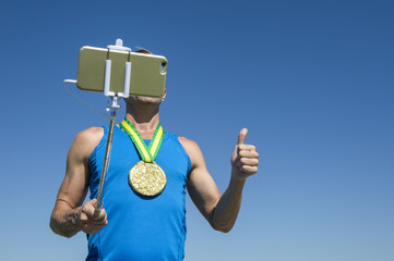 Gold medal athlete posing for a selfie with a mobile phone on a selfie stick