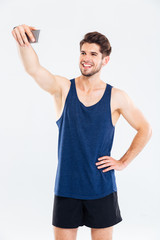 Smiling young sportsman standing and talking selfie with cell phone