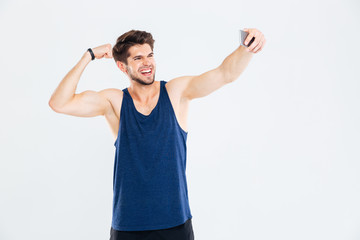 Cheerful young sportsman showing biceps and taking selfie with smartphone