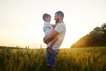 Father holding small son in field during beautiful sunset
