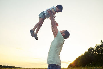 Happy father lifting his small son on background of sunset sky