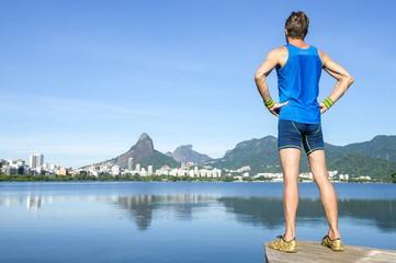 Athlete in blue sport uniform standing in front of Rio de Janeiro Brazil skyline at Lagoa Rodrigo de Freitas lagoon