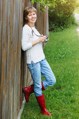 Girl in a white sweater and  in red rubber boots with retro photo camera near the fence outdoors