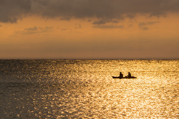 Silhouette of a couple on a canoe boat during sunset