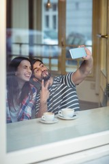 Cheerful couple taking selfie at cafeteria
