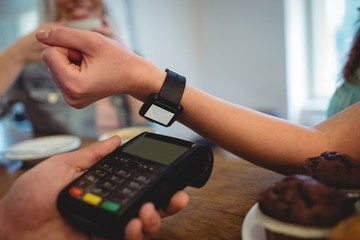 Cropped image of customer with smart watch at cafe