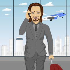 business man talking on smartphone at airport standing with with luggage