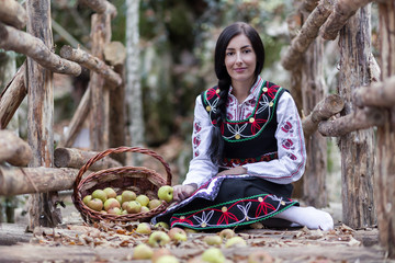 oung girl with bulgarian costume sitting on the ground with basket with apples