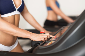 Woman set level on treadmill in gym