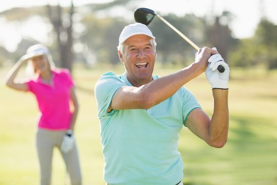 Portrait of cheerful mature golfer holding golf club