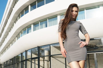 Brunette Asian woman wearing striped dress standing in front of the white building in the city