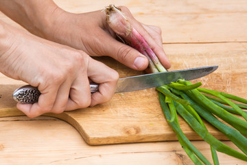 hands chopping green onion on the wooden cutting board